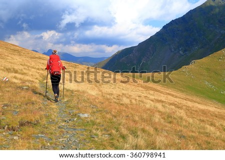 Backpacker woman departing on sunny mountain trail in fine day - stock photo