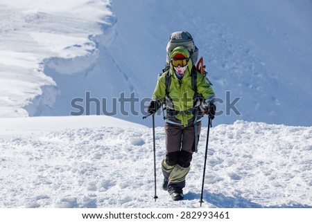 Backpacker woman is walking in winter mountains on sunny day - stock photo