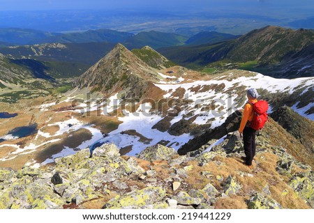 Backpacker woman standing on aerial mountain ridge in fine day - stock photo