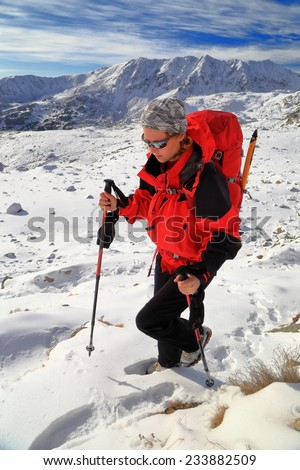 Backpacker woman walking on snow covered field on the mountains - stock photo