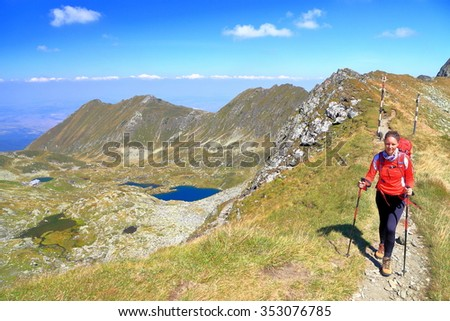 Backpacker woman walking on top of sunny mountain ridge in sunny day of summer - stock photo