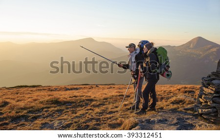 Backpackers couple hiking during fall. Man and woman standing on beautiful mountain summit, man is pointing to the distance with trekking stick. Mountains on the background.