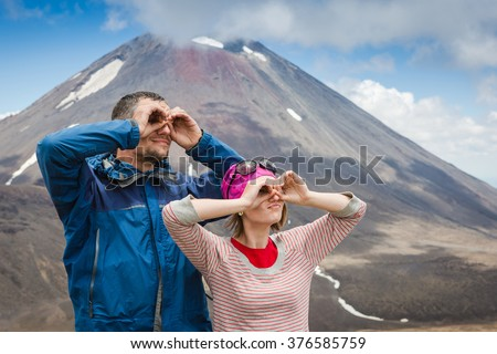 Backpackers couple hiking in New Zealand and have fun. Caucasian hiker couple enjoying themselves on summer vacation - stock photo