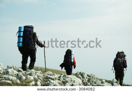 Backpackers going up along hill - stock photo