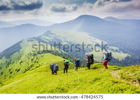 Backpackers hiking on the path in summer mountains
