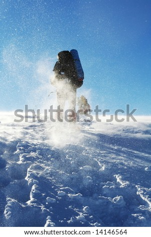 Backpackers in winter mountain - stock photo