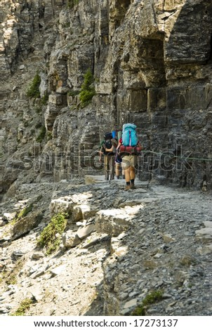 backpackers on the Highline Trail in Glacier National Park - stock photo