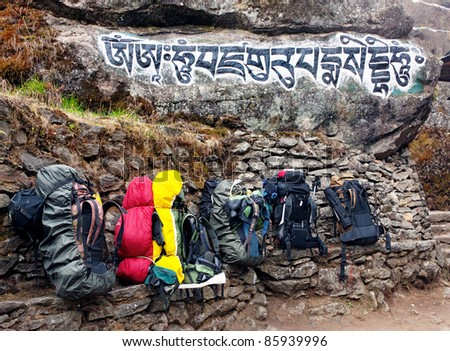 Backpacks tourists and a buddhist mantra carved on the rock in Nepal - stock photo