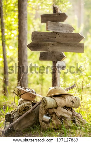 Backpacks travelers under the roadway pointer on a forest road - stock photo