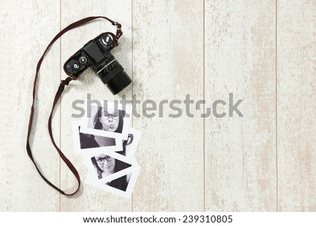 Backround with an vintage camera and some black and white retro photographs on a wooden surface - stock photo