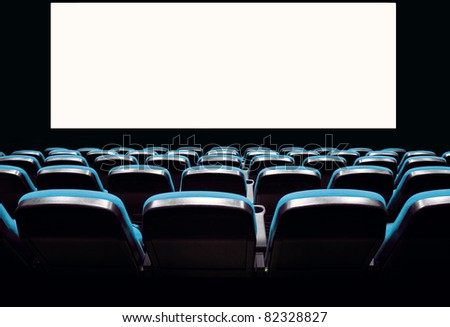 Backs of empty blue seats in a movie theater with a white screen - stock photo