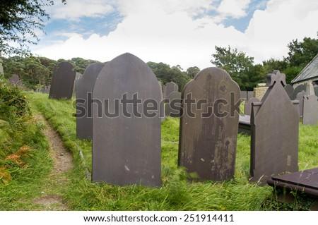 Backs of gravestones, made from dark blue slate. Menai Bridge, Anglesey, Wales, United Kingdom. - stock photo