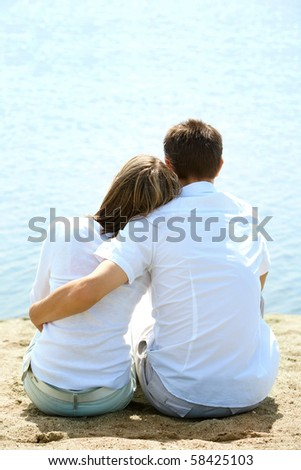 Backs of serene couple sitting on sandy shore in front of blue water - stock photo