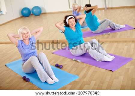 Backs of sporty females doing physical exercise for belly  - stock photo