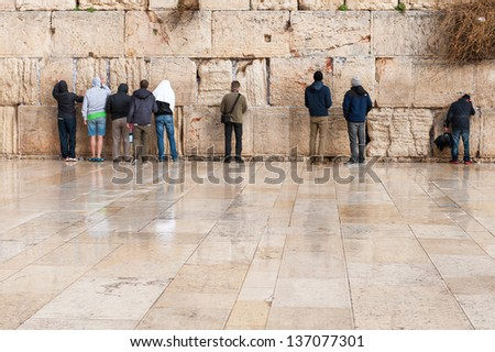 Backs of unidentified young prayers standing at the Western wall in Jerusalem, Israel - stock photo