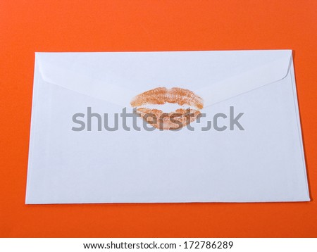 backside of white envelope with orange lipstick kiss on orange background - stock photo