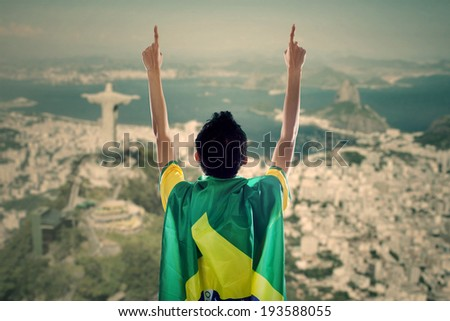Backside of young man with a Brazilian flag on his back celebrating the competition time - stock photo