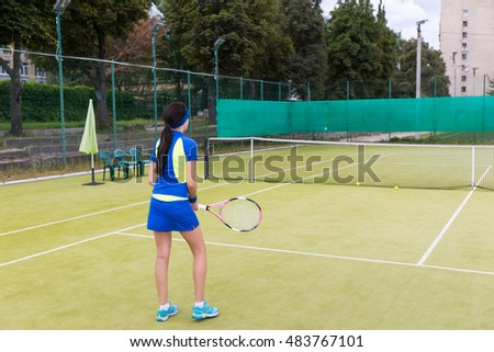 Backside view of beautiful sporty girl wearing a sportswear playing a match on the court on a sunny day