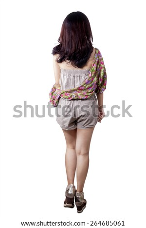 Backside view of young girl with casual clothes walking forward, isolated over white background - stock photo