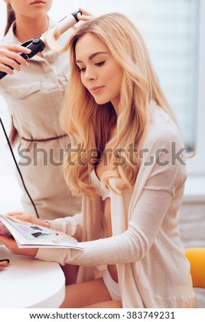 Backstage. Beautiful young woman reading magazine while hairstylist curling her hair with curling wand in make-up room - stock photo