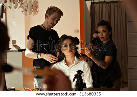 Backstage prepare young beautiful modeling stylist hairdresser and makeup artist working on models in the way of professional beauty salon. Work up artist and hairdresser at the salon- stock photo.