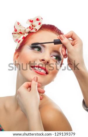 Backstage scene: Professional Make-up artist doing pinup model makeup at work - stock photo