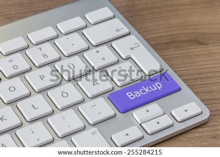 Backup written on a large blue button of a modern keyboard on a wooden desktop - stock photo