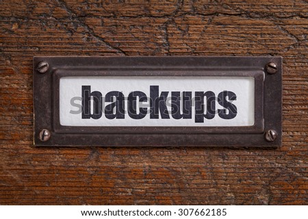 backups - a label on a grunge wooden file cabinet