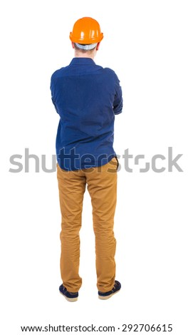 Backview an engineer in construction helmet stands. Standing young guy. Rear view people collection.   Isolated over white background. young engineer standing with his arms crossed and evaluates work. - stock photo