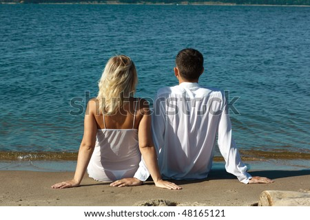 backview of romantic slavonic couple - blonde girl in peignoir and brown haired man in white shirt taking their time on the beach - stock photo