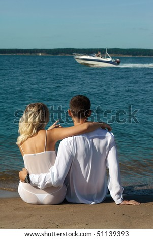backview of romantic slavonic couple - blonde girl in peignoir and brown haired man in white shirt taking their time on the beach. girl points on the cutter, speeding on background - stock photo