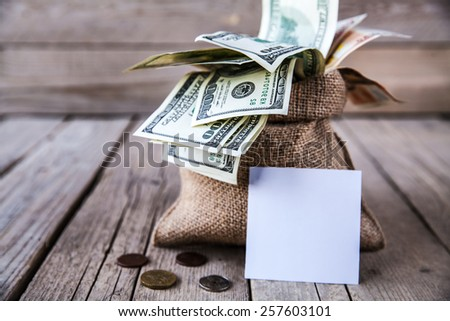 backwards money and a piece of burlap for notes on the wooden background - stock photo