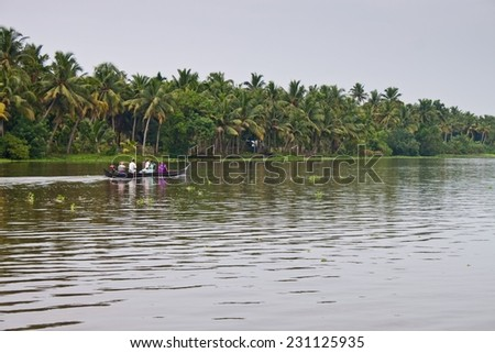 BACKWATERS, INDIA - AUGUST 24: People in a canoe on August 24, 2011 in Backwaters, India. The Kerala Backwaters are a network of interconnected canals, rivers, lakes and inlets.