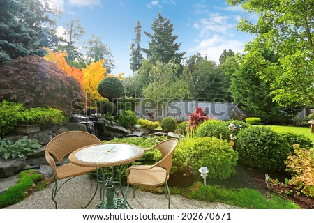 Backyard area with table and wicker chairs surrounded by tropical garden with waterfall - stock photo