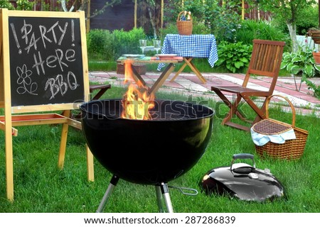 Backyard BBQ Grill Party Scene.Chalkboard With Sign Party Here BBQ, Flaming Grill, Wood Outdoor Furniture, Garden Decoration, Wine, Picnic Basket - stock photo