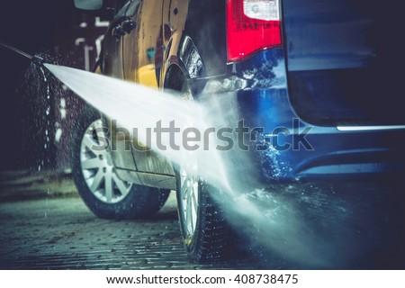 Backyard Car Washing Closeup Photo. Power Washing and Cleaning Family Van. - stock photo