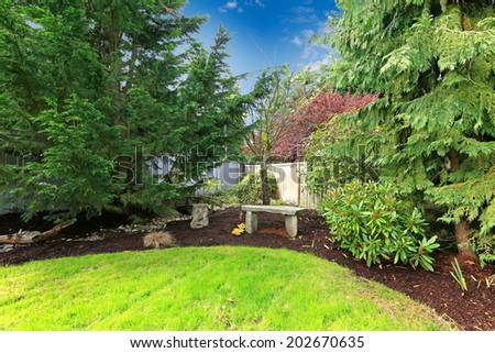 Backyard landscape with green lawn,trees and stone bench