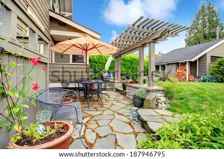 Backyard patio area with umbrella and pergola - stock photo
