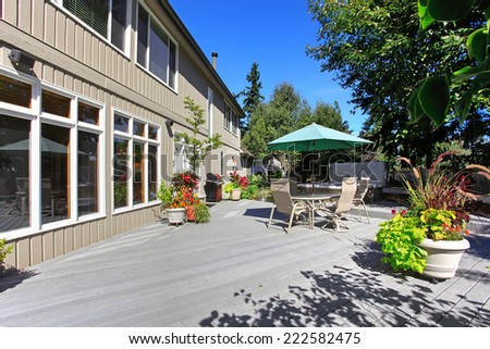Backyard patio with table set and jacuzzi. Patio decorated with flower pots - stock photo