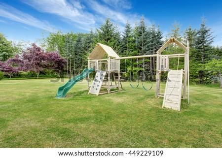 Backyard playground with swings, climbing wood panel, chute. - stock photo