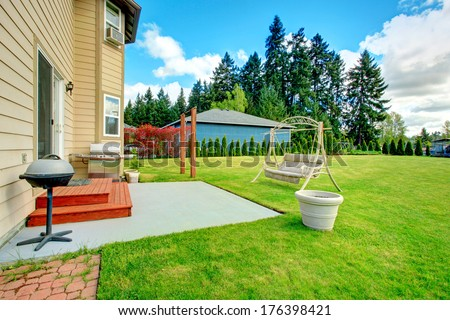 Backyard small patio area with swing, large green lawn with fir trees and garden bed - stock photo