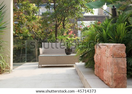 Backyard with cane chair and tree in a Garden - stock photo