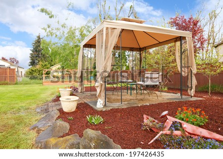 Backyard  with flower beds, lawn and gazebo - stock photo