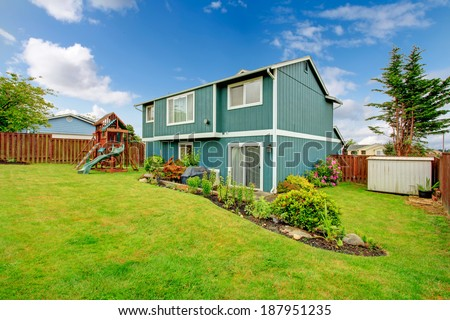 Backyard with green lawn, flower beds and playground for kids - stock photo