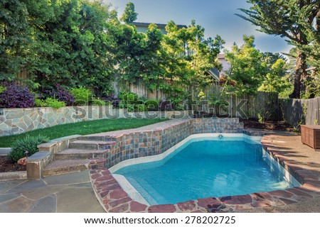 Backyard with outdoor in ground residential swimming pool, garden, deck and stone patio. - stock photo