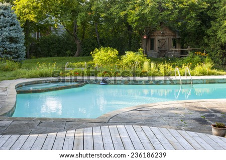 Backyard with outdoor inground residential swimming pool, garden, deck and stone patio - stock photo