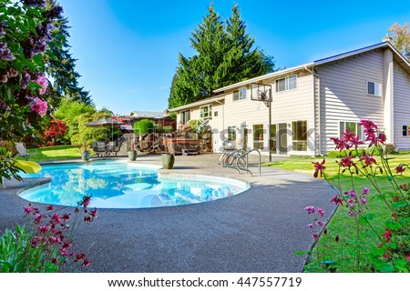 Backyard with small beautiful swimming pool, hot tub, patio area, chairs and basketball hoop - stock photo