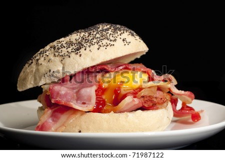 Bacon and egg roll with tomato sauce with a black background. - stock photo