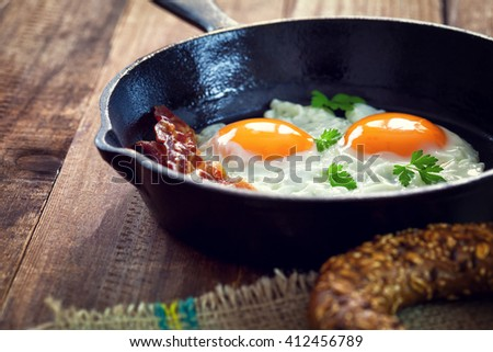 Bacon and Eggs for breakfast in iron skillet - stock photo