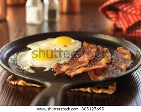 bacon and eggs fried in iron skillet - stock photo